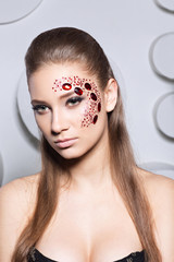 creative fashion girl with red stones on the face, contrast