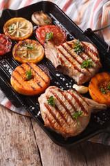 Grilled pork, pumpkin and lemon on a grill pan. Vertical