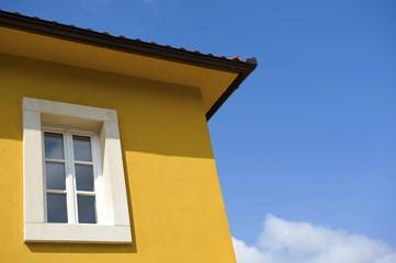 White window on yellow house