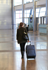 Young woman with blue suitcase at an airport