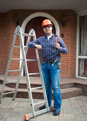 worker posing with tools against house entrance