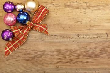 Schleife und Christbaumkugeln auf Holz