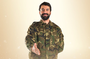 Soldier making a deal over white background