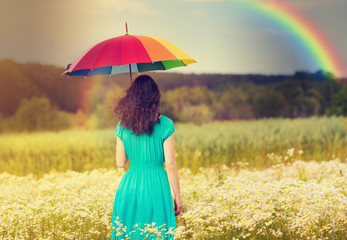 Young woman walking on the field under umbrella in fair weather