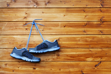 pair of sport shoes hang on a nail on a brown wooden wall