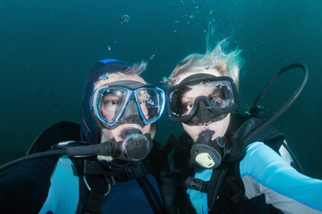 Wall Mural - beautiful blonde girl and male diver looking at you underwater