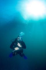 Wall Mural - Scuba diver underwater portrait in the deep blue ocean
