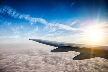 Fotobehang - Wing of the plane on blue sky background