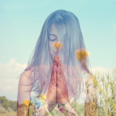 double exposure of a young woman meditating and a peaceful lands