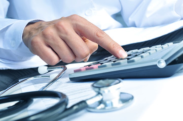 healthcare professional calculating on an electronic calculator