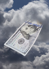 One hundred dollar bill in US currency coming from the sky.