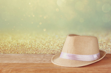 fedora hat over wooden table and glitter background