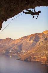 Male rock climber climbing along roof in cave, Kalymnos Island, Greece
