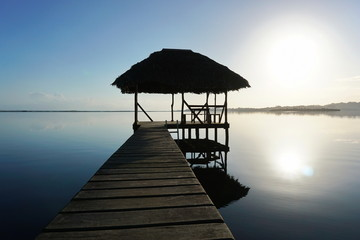 Dock with tropical hut over water on sunrise light