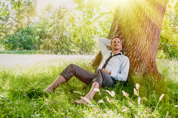 handsome grey hair man taking a break, barefoot in the grass