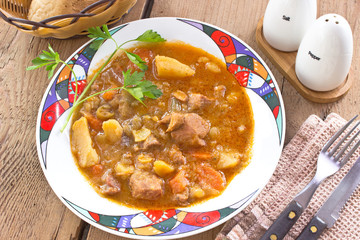 Pork stew in plate on wooden table
