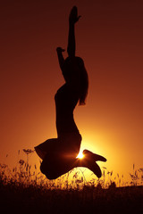 Silhouette of happy woman jumping in sunset