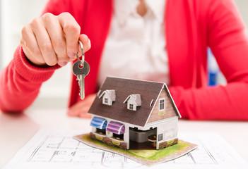 Female makler holding key of apartment. Real estate rent concept