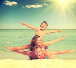 Wall Mural - Happy family having fun at the beach. Joyful family