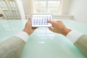 Fototapete - Businessman Looking At Calendar On Digital Tablet