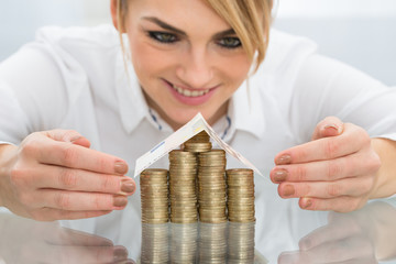 Businesswoman Covering House Of Coins