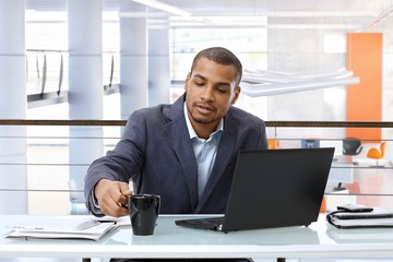 Black businessman working with computer in office