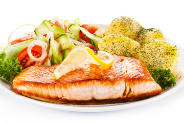 Fried salmon and vegetables on white background