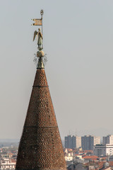 Bronze winged statue holding a Visconti flag on top of bell towe