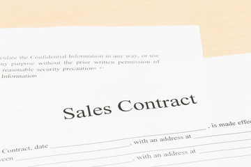 Sales contract on desk; document is mock-up