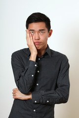 Frustrated young Asian man covering his face with a palm