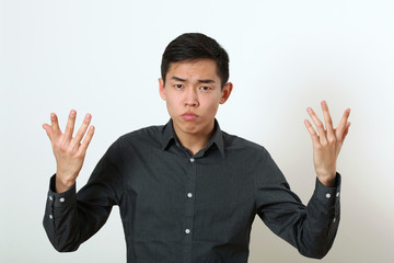Displeased young Asian man gesturing with two hands