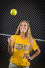Female Softball Player Portrait with Ball in the Air.