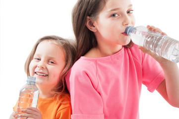 Little girls drinking mineral bottle of water