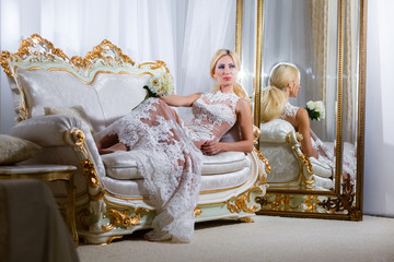 Woman in a magnificent dress lying on the sofa and mirrors