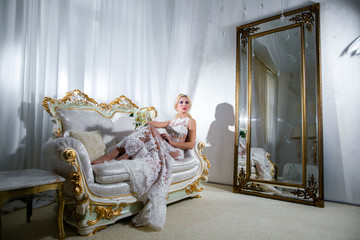 Girl in a luxurious dress lying on the sofa and mirrors