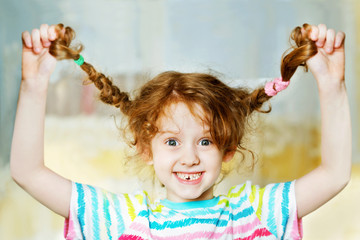 Laughing girl pull her pigtail up by hand and show her teeths.