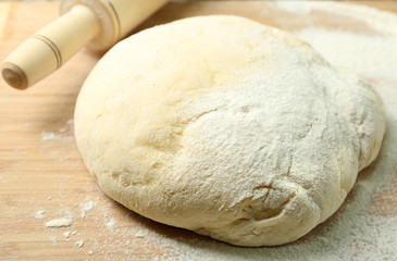 Dough on cutting board with rolling pin close up
