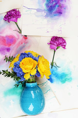 Beautiful flowers in vase on watercolor sketches background top view