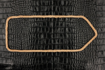 Arrow made of rope  lies on a background of crocodile  leather