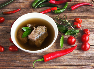 Beef broth with meat with vegetables on wooden background