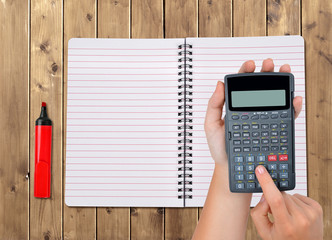 Hands with calculator in the background notebook on wooden table