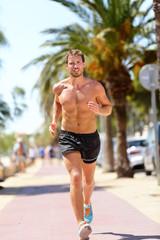 Fit man runner training cardio running in city