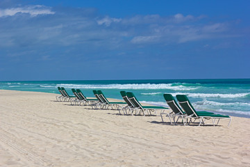 Fototapete - Miami Beach with rolling waves and empty beach chairs.