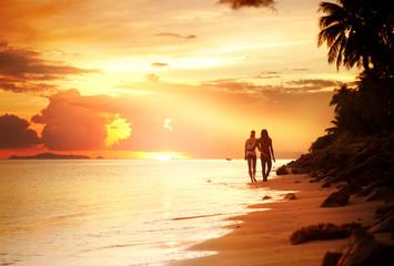 Lovers walk along the beach at sunset