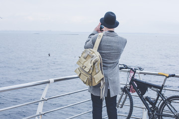 handsome young hipster guy in hat taking picture of the sea
