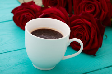 Espresso cup of Coffee and red roses on blue wooden table. Selective focus