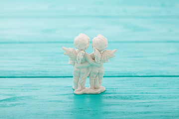 Cupids on blue wooden background.Selective focus