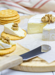 Soft brie cheese with crackers and nuts
