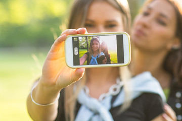 Two young trendy girls doing selfie.