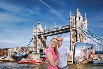 couple taking selfie against Tower Bridge in London, England